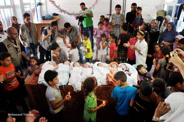 In una delle scuole dell'UNRWA si celebra, una settimana dopo, la nascita di alcuni bambini appartenenti a famiglie di sfollati. Gaza, 19 agosto 2014, foto di Mohammed Talatene.