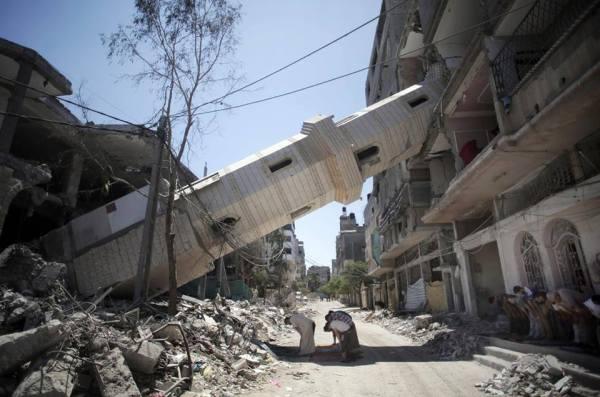Palestinesi in preghiera vicino a una moschea distrutta dai bombardamenti israeliani, a Gaza. (Khalil Hamra, Ap/Lapresse)